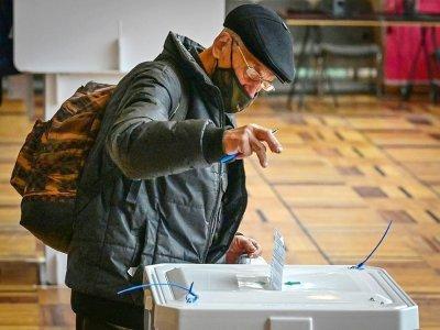 Un homme glisse son bulletin dans l'urne le 17 septembre 2021 à Moscou - Yuri KADOBNOV [AFP]