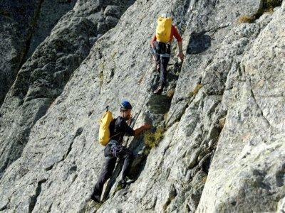 David Labarre (à gauche) sur la paroi rocheuse du pic des Spijeoles, dernière ascension de son défi - VALENTINE CHAPUIS [AFP]