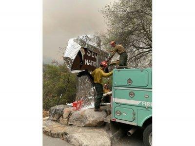 Des pompiers enveloppent d'une couverture ignifugée le panneau d'accueil du parc national de Sequoia, le 16 septembre 2021, en Californie - Handout [NATIONAL PARK SERVICE/AFP]
