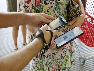 Une employée d'un centre commercial vérifie le pass sanitaire d'une cliente à Ajaccio, en Corse, le 16 août 2021 - Pascal POCHARD-CASABIANCA [AFP]