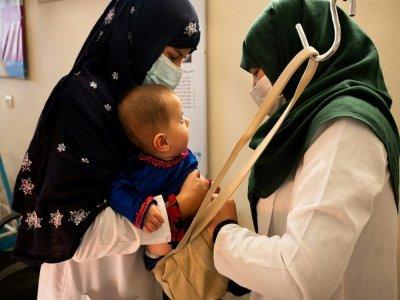 Une sage-femme et une diététicienne pèsent un bébé à la clinique de Tangi Saidan, le 6 octobre 2021 en Afghanistan - Elise BLANCHARD [AFP]