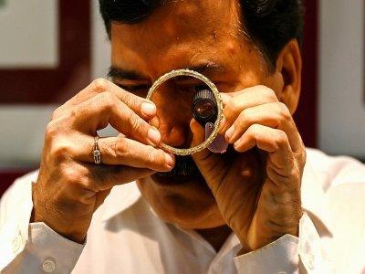 Un gérant de bijouterie examine à la loupe un bracelet en or, le 11 octobre 2021 à Bombay, en Inde - Punit PARANJPE [AFP]