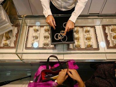 Un gérant de bijouterie montre des bracelets à une cliente, le 11 août 2021 à Bombay, en Inde - Punit PARANJPE [AFP]