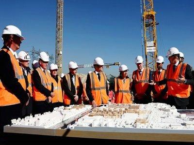 Le président Emmanuel Macron (au centre) et le premier ministre Jean Castex ainsi que la maire de Paris Anne Hidalgo se font présenter la maquette du village olympique à Saint-Ouen, le 14 octobre 2021 - SARAH MEYSSONNIER [POOL/AFP]